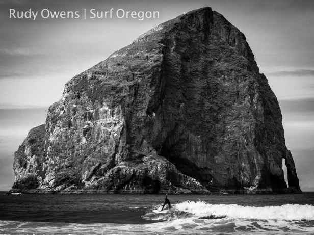 A surfer catches a clean break at Pacific City, south of Cape Kiwanda, Oregon.