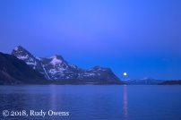 A full moon rises over Nuuk's harbor.
